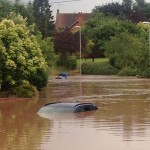 © newsteam Summer soaking: A car is almost completely covered by muddy water after a downpour caused flash flooding in Southwell, Nottingham, yesterday