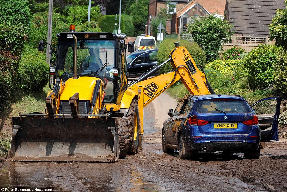 © Peter Summers / Newsteam 24/07/2013 Clear-up: A digger is brought in to clear some of the mud and dirt away after an entire street in Southwell, Nottinghamshire was submerged in water