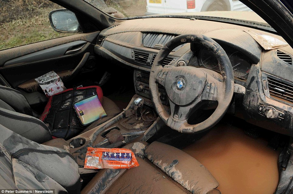 © Peter Summers / Newsteam 24/07/2013 Wrecked car: This BMW is covered in dirt and the footwell submerged in water as flash floods hit in Southwell, Nottinghamshire