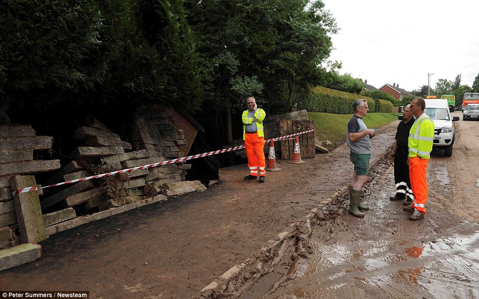© Peter Summers / Newsteam 24/07/2013 Destruction: Workers begin to repair the damage after heavy rain caused the river to burst its banks in Southwell and flooded an entire street
